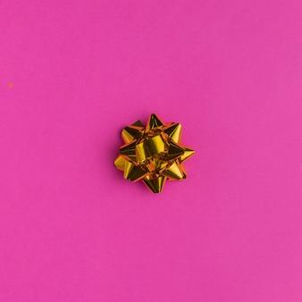 Złoty prezent łęk na jaskrawym różowym tle