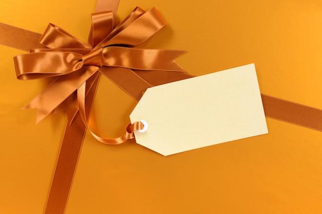 Złoty prezent na boże narodzenie w tle z tagiem prezent