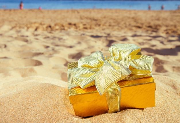 Złoty prezent świąteczny na plaży