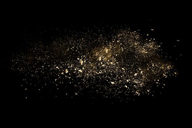 Złoty prochowy wybuch na czarnym tle.
