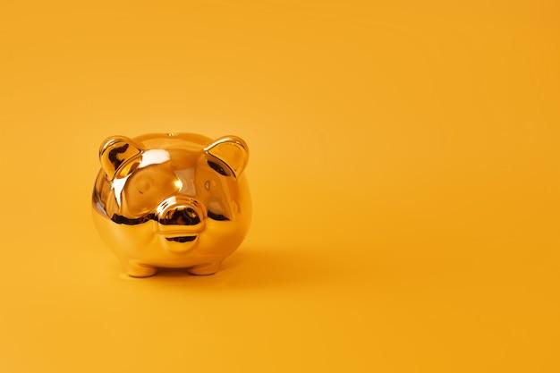 Złoty prosiątko bank na żółtym tle. złota skarbonka