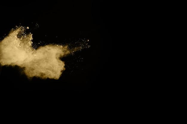 Złoty proszek wybuch na czarnym tle. zamrozić ruch.