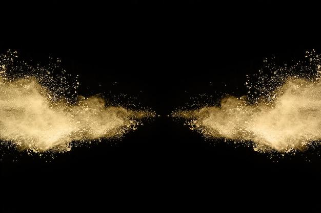 Złoty proszek wybuch na czarnym tle.