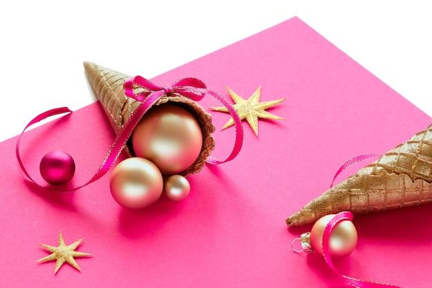 Złoty rożek do lodów waflowych z bombkami, gwiazdkami i wstążkami na różowym papierze
