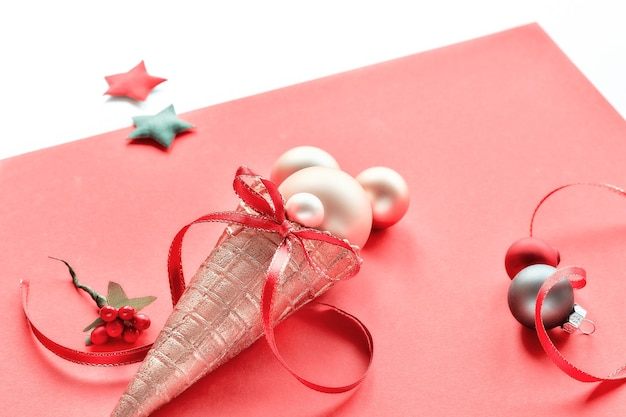 Złoty rożek waflowy z bożonarodzeniowymi złotymi bibelotami, gwiazdkami i czerwonymi wstążkami na różowym papierze