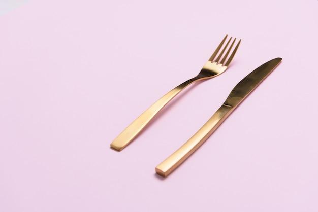 Złoty rozwidlenie i nóż na świetle - różowy tło z negatyw przestrzenią