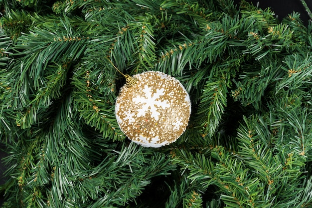 Złoty śnieg christmas ball na białym tle na gałęzi choinki.