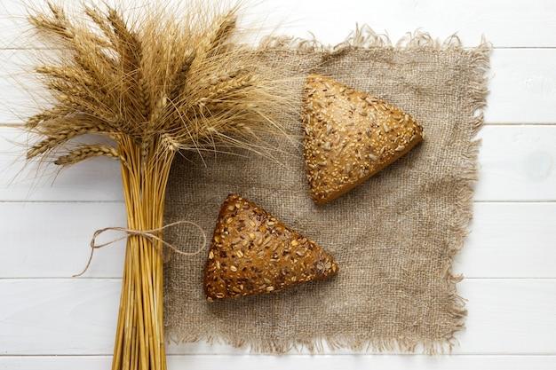 Złoty świeży chleb rękodzieła lub bułki z ucho pszenicy na białym stole.