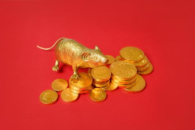 Złoty szczur zodiaku i stos złotych monet z czerwonym tle, szczęśliwego nowego roku chińskiego.
