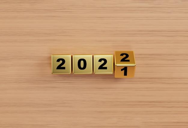 Złoty sześcian blokowy przerzucający się między 2021 a 2022 r. na tle drewnianego stołu dla zmiany i przygotowania wesołych świąt i szczęśliwego nowego roku przez renderowanie 3d.