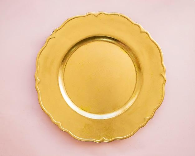 Złoty talerz na różowym stole