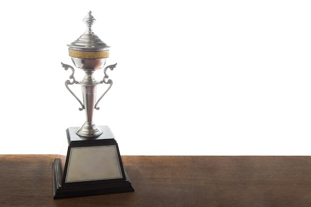 Złoty trofeum na drewnianym stole odizolowywającym nad białym tłem. zwycięskie nagrody