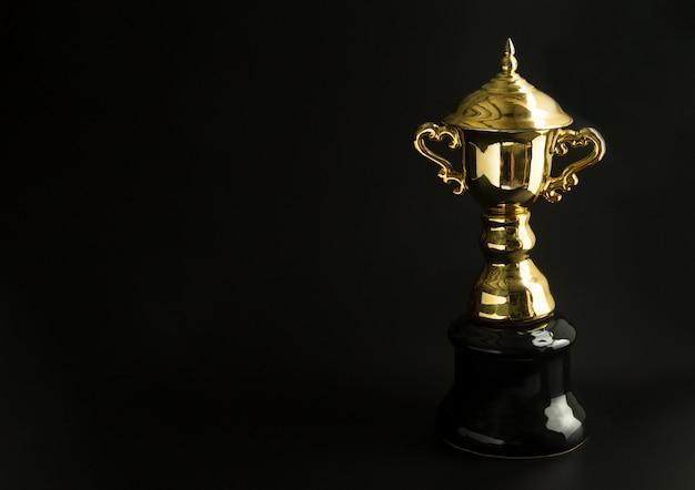 Złoty trofeum nad czarnym tłem. zwycięskie nagrody