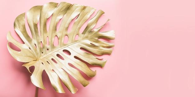 Złoty tropikalny liść palmowy monstera na luksusowym pastelowym różu.