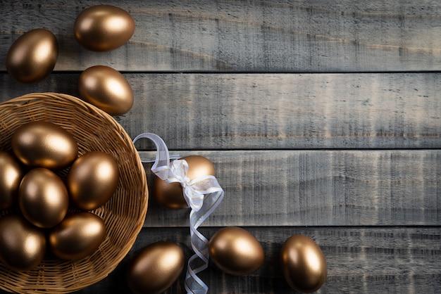 Złoty wielkanocni jajka w gniazdeczku i piórko na drewnianym tle.