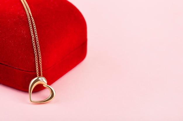Złoty wisiorek w kształcie serca na czerwonym pudełku