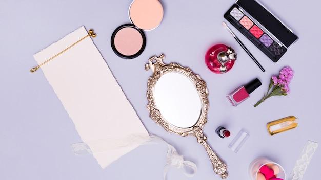 Złoty włosiany kij na pustym bielu drzejącym papierze z kosmetycznymi produktami i ręki lustrem na purpurowym tle