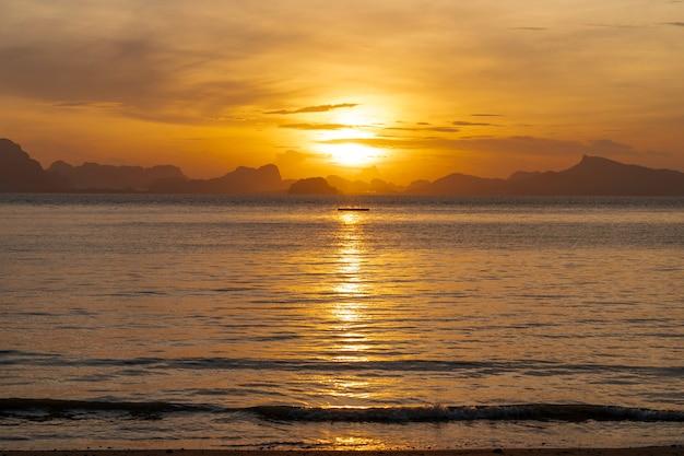 Złoty wschód słońca rano na wybrzeżu morza z odbiciem promieni słonecznych na spokojnym morzu małej fali w koh yao noi