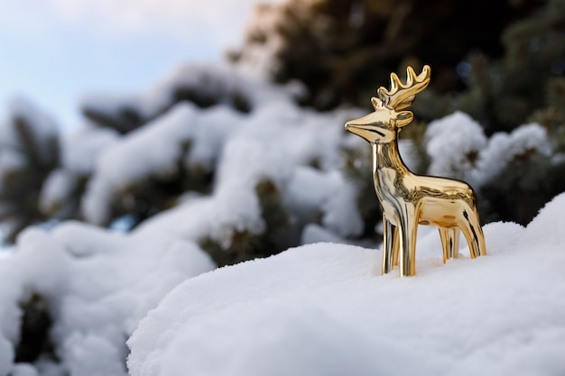 Złoty zabawkarski jeleń stoi na śnieżnej gałąź wiecznozielona sosna na niebieskim niebie