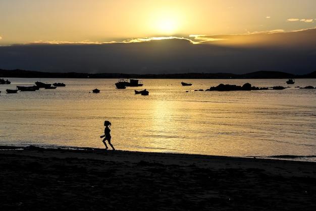 Złoty zachód słońca na plaży, podświetlana dziewczyna biegnie nad brzegiem morza