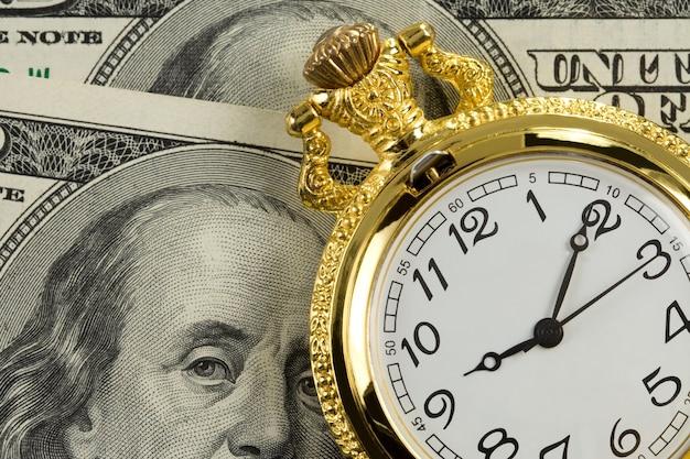 Złoty zegarek na banknotach dolarowych