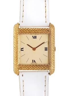 Złoty zegarek z białym skórzanym paskiem pod światłami na białym tle