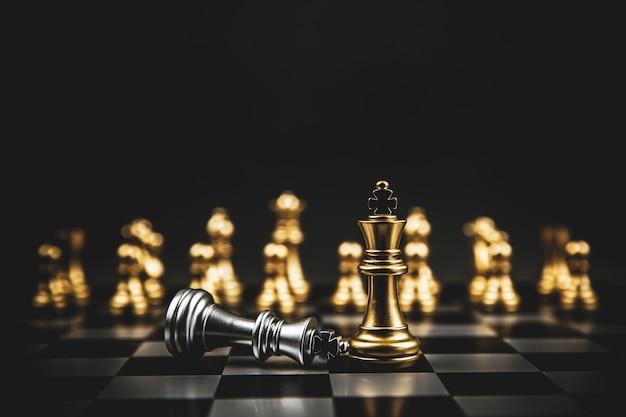 Złoty zespół szachowy stojący na szachownicy.