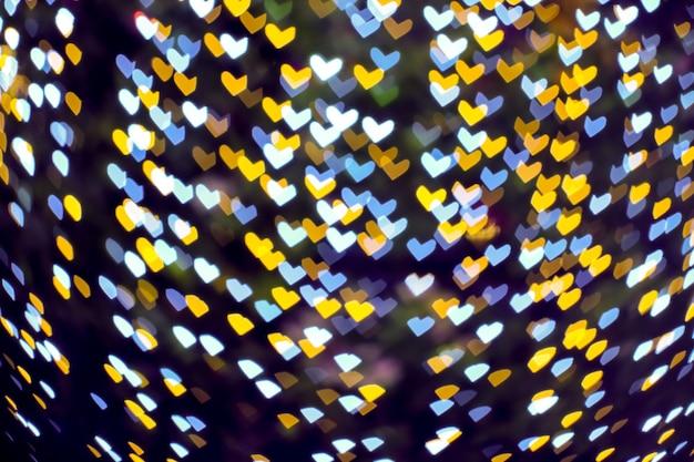 Złoty żółty rozmycie serca kształt miłość walentynki światło nocne na drzewie w ogrodzie