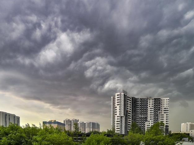 Złowieszcze burzowe niebo z maczugami ciężkich chmur nad wielopiętrowymi domami miejskimi