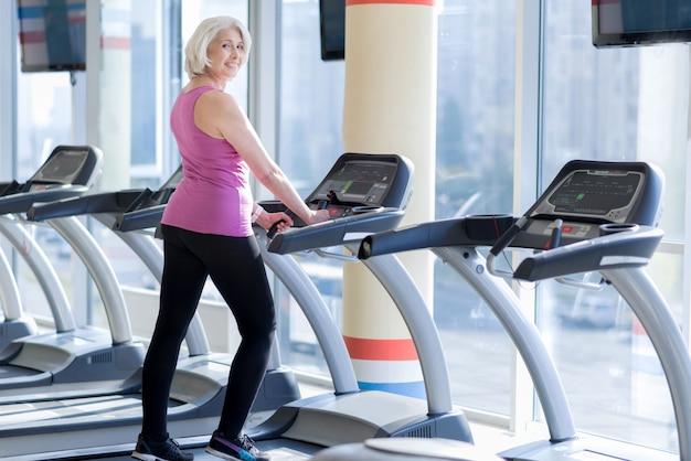 Złożenie zdrowe. szczęśliwy szczęśliwy starszy kobieta uśmiecha się i robi ćwiczenia na bieżni podczas treningu na siłowni.