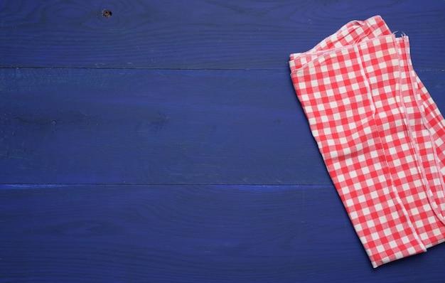 Złożona biało-czerwona bawełniana serwetka kuchenna na drewnianym niebieskim tle, widok z góry, kopia przestrzeń