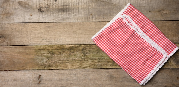 Złożona biało-czerwona bawełniana serwetka kuchenna na drewnianym szarym tle, widok z góry
