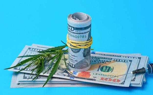 Złożona gotówka w dolarach amerykańskich, zielony liść konopi