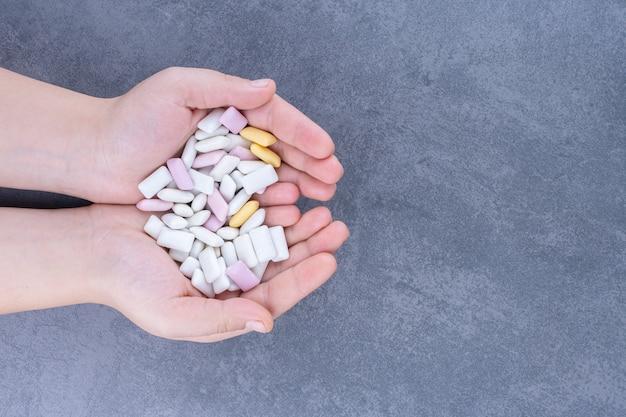 Złożone dłonie trzymające mały stos tabletek do żucia na marmurowej powierzchni