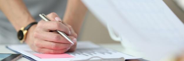 Złożone dłonie trzymające obok długopis to raport z komercyjnymi wykresami