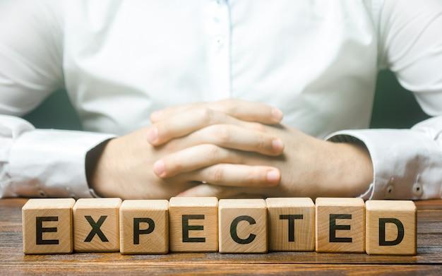 Złożone ręce na tle słowa oczekiwana koncepcja przewidywania i przewidywania bądź przygotowany