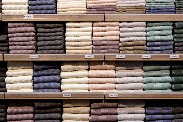Złożone wielokolorowe ręczniki na półkach. starannie złożone ubrania. stojak na ubrania z ciepłym. bawełniane ręczniki starannie złożone