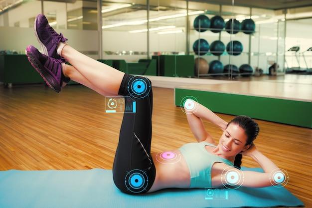 Złożony obraz wysportowanej brunetki wykonującej siadanie w studio fitness