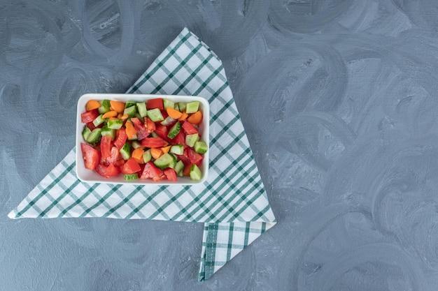 Złożony obrus pod miską sałatki pasterskiej zmieszanej z plastrami marchwi na marmurowym stole.
