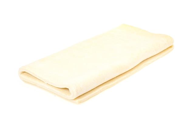 Złożony talerz surowego ciasta na białym tle.