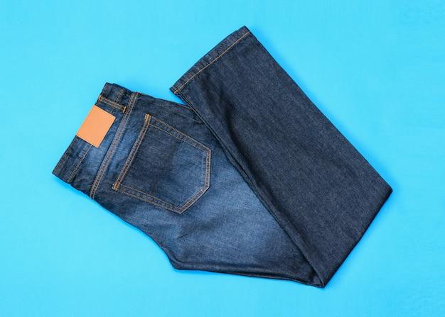 Złożony w pół niebieskie dżinsy męskie na niebieskim stole. widok z góry. leżał płasko.