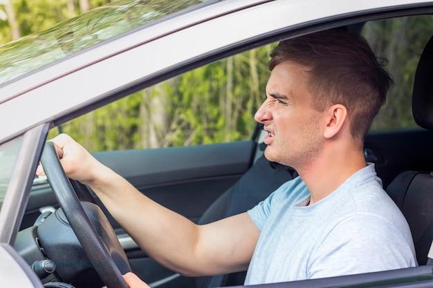 Zły, agresywny, szalony młody człowiek, kierowca, sfrustrowany niezadowolony wściekły facet prowadzący samochód, problemy na drodze, korki. uszkodzony samochód, koncepcja agresji. portret wzburzona samiec wśrodku samochodu