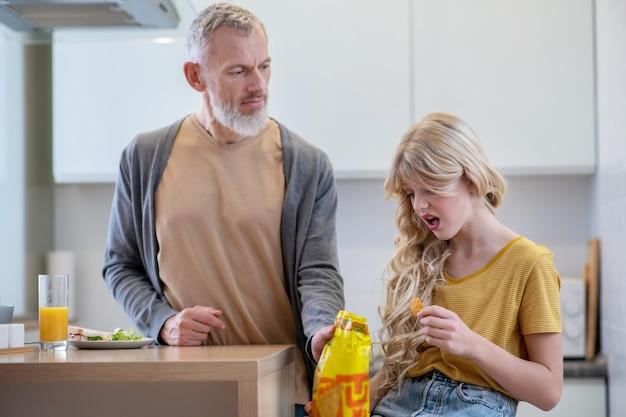 Zły apetyt. tata próbuje zmusić córkę do jedzenia śniadania