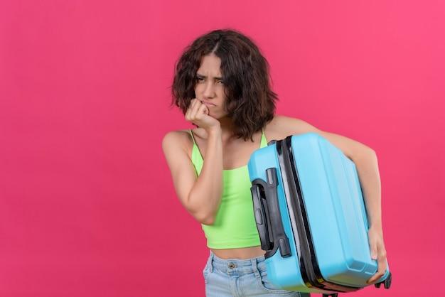Zły, atrakcyjna kobieta z krótkimi włosami, ubrana w zielony krótki top, trzymając niebieską walizkę, patrząc wściekły