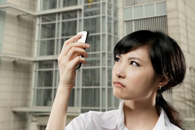 Zły biznes kobieta z azji trzymając telefon komórkowy i patrząc na to