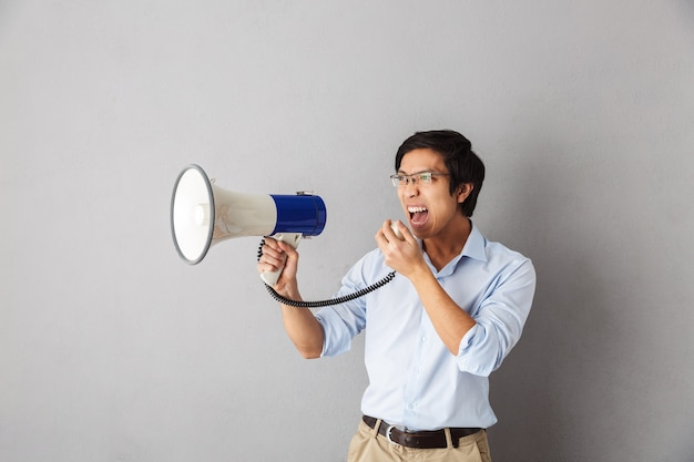 Zły biznesmen azjatyckich stojący na białym tle, krzycząc na głośnik