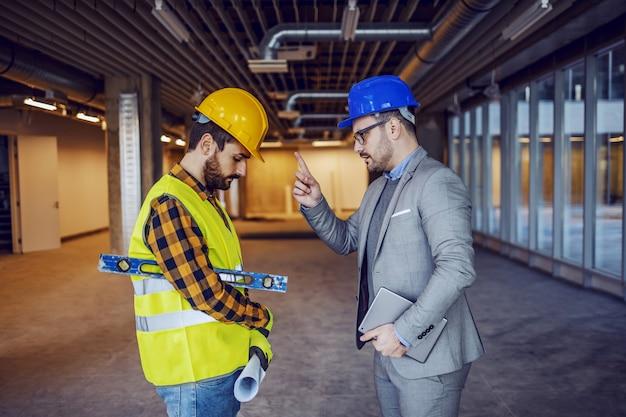 Zły biznesmen kaukaski w garniturze i kasku na głowie kłóci się z nieodpowiedzialnym pracownikiem budowlanym. budynek w trakcie budowy wnętrza.
