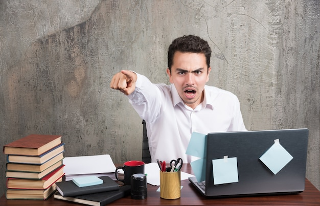 Zły biznesmen rozmawia z telefonem w biurze informacji turystycznej.