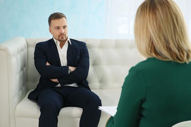 Zły biznesmen siedzi na kanapie rozmawiając z kobietą psychologiem.