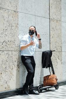 Zły biznesmen, stojąc na zewnątrz i rozmawiając przez telefon z pracownikiem
